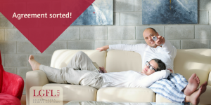 two people on sofa with remote in hand